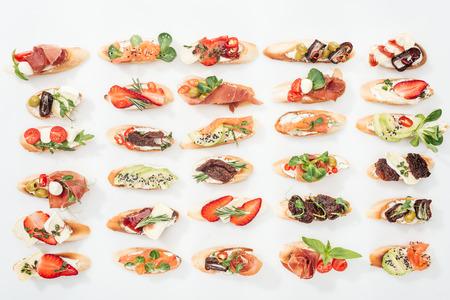 background of italian bruschetta with salmon, prosciutto, dried tomatoes, avocado, strawberries and herbs on white Stock Photo