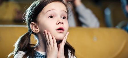 photo panoramique d'un enfant émotif regardant un film et se tenant la main près du visage