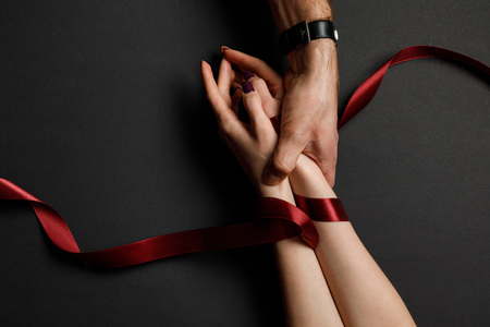 cropped view of man holding female hands in red satin ribbon on black background