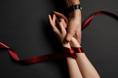 vue recadrée de l'homme tenant les mains des femmes en ruban de satin rouge sur fond noir Banque d'images