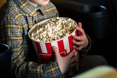 partial view of boy holding paper cup with popcorn while sitting in cinema