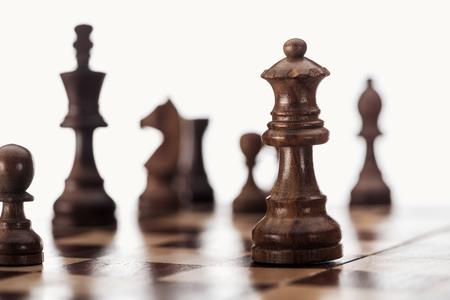 selectieve focus van houten schaakbord met donkerbruine schaakfiguren geïsoleerd op wit