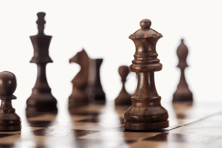 selective focus of wooden chessboard with dark brown chess figures isolated on white