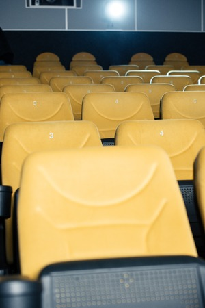 rows of comfortable, numbered orange seats in cinema hall Imagens