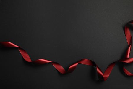 top view of red silk wavy ribbon on black background with copy space Stock Photo