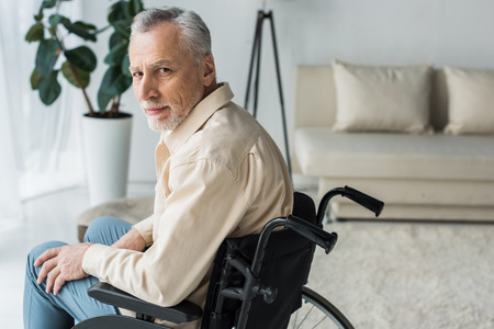disabled retired man sitting in wheelchair at home and looking at camera