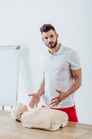 handsome man gesturing and looking at camera during cpr training with dummy Stock Photo
