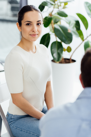 selective focus of woman sitting and looking at camera during therapy session