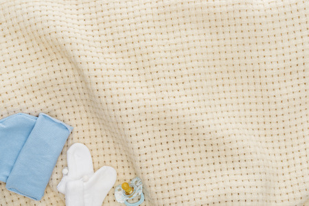 top view of pacifier, hat, booties on beige blanket with copy space Stockfoto