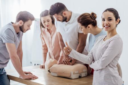 woman showing thumb up while group of people performing cpr on dummy during first aid training Standard-Bild