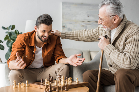 retired father in glasses putting hand on shoulder of happy son while playing chess