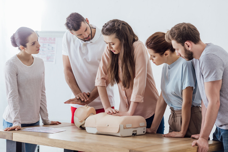 group of concentrated people performing cpr on dummy during first aid training