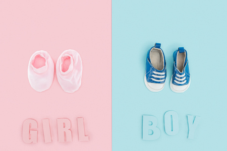 top view of boy and girl lettering and sneakers, booties on pink and blue background Stockfoto