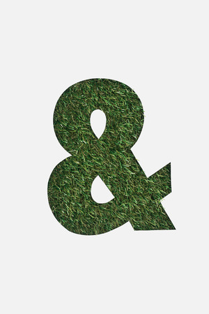 top view of cut out Ampersand sign on green grass background isolated on white