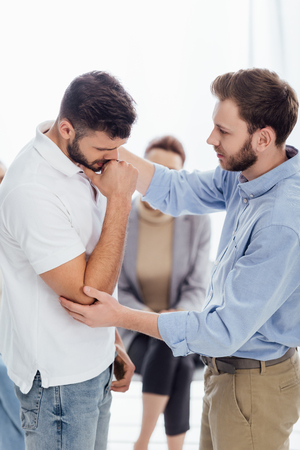 selective focus of man consoling upset man during therapy meeting