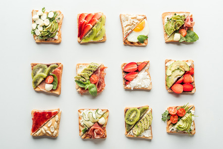 top view of tasty toasts with fruits, vegetables and basil isolated on white Фото со стока