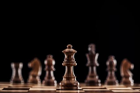 Selektiver Fokus der braunen Holzkönigin auf dem Schachbrett isoliert auf Schwarz Standard-Bild