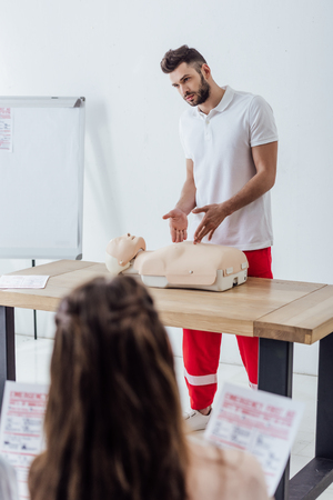 handsome instructor gesturing with hands during first aid training class