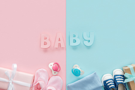 top view of pacifiers, gifts, hat, booties, sneakers and baby lettering Stockfoto