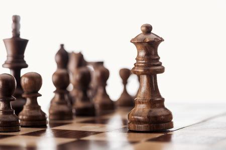 El enfoque selectivo del tablero de ajedrez de madera con figuras de ajedrez aislado en blanco