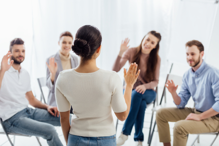 people sitting and raising hands during group therapy session