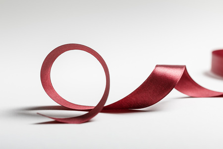 silk curved burgundy ribbon on grey background