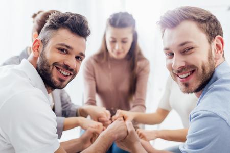 grupa osób siedzących, uśmiechających się i układających ręce podczas sesji terapeutycznej
