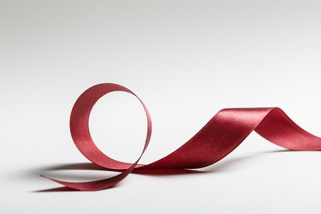 shiny silk wavy burgundy ribbon on grey background