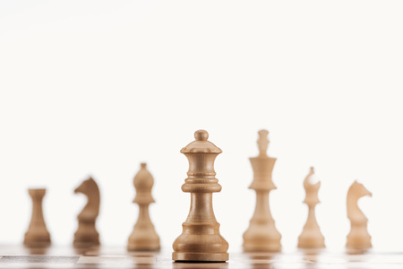 selective focus of beige wooden queen on chessboard isolated on white Фото со стока
