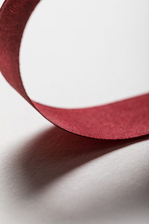 close up of shiny silk wavy burgundy ribbon on grey background Stock Photo