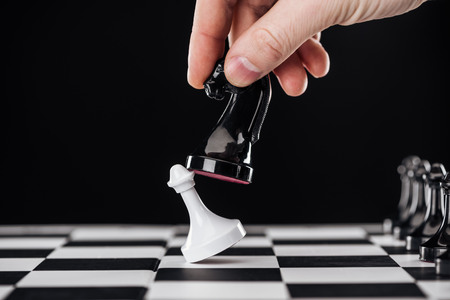 partial view of man doing move with knight on chessboard isolated on black