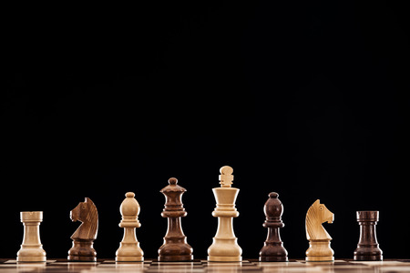 houten schaakbord met bruine en beige schaakstukken geïsoleerd op zwart