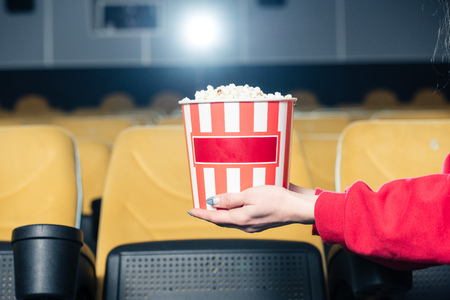 partial view of child holding stripped paper cup with popcorn in cinema
