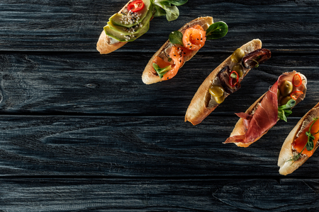 top view of italian bruschetta with salmon, prosciutto and olives on wooden table Stock Photo