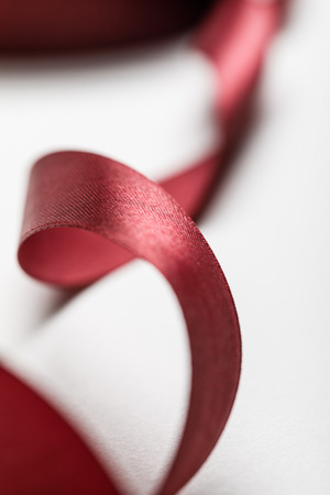 close up of silk wavy burgundy ribbon on grey background