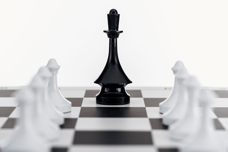 selective focus of chessboard with black queen figure among white pawns isolated on white