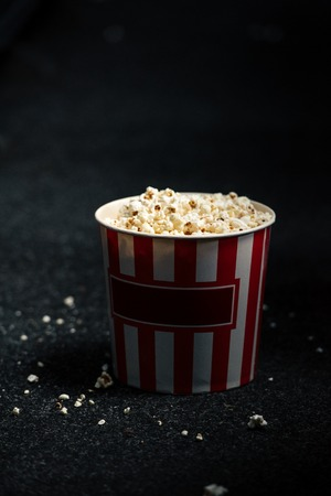 stripped red and white paper cup with popcorn on cinema hall floor