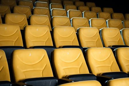 rows of comfortable orange empty seats in cinema hall