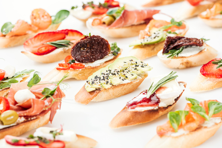 selective focus of italian bruschetta with dried tomatoes, avocado, prosciutto and herbs Stock Photo