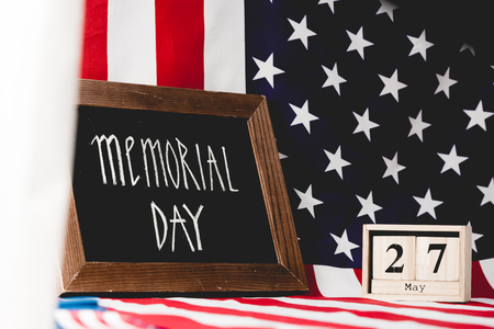 black board with memorial day letters near flag of america and cubes with date