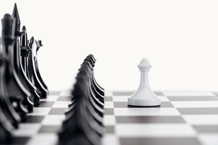 selective focus of chessboard with black chess figures and white pawn in front isolated on white
