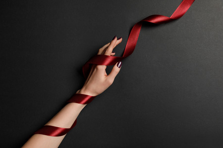 cropped view of female hand and satin red ribbon on black background Stock Photo