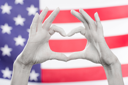 cropped view of female hands painted in white showing heard-shaped sign near flag of america