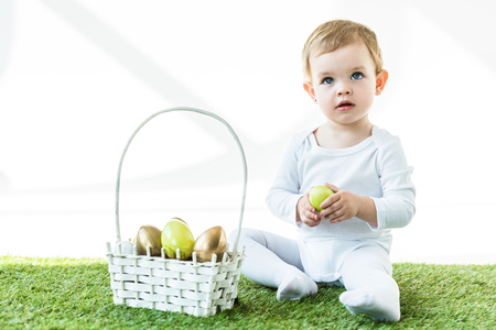 cute blonde baby holding yellow chicken egg while sitting near straw basket with Easter eggs  isolated on white Zdjęcie Seryjne