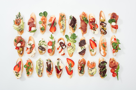 background of traditional italian bruschetta with salmon, prosciutto, dried tomatoes, avocado, strawberries and herbs on white