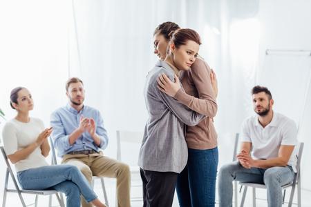 kobiety przytulające się, podczas gdy grupa ludzi siedzi i bije brawo podczas sesji terapeutycznej