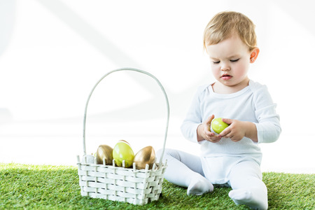 adorable blonde child holding yellow chicken egg while sitting near straw basket with Easter eggs isolated on white