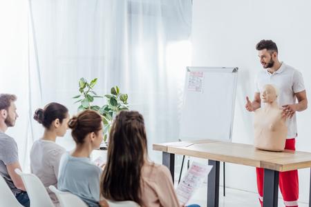 gut aussehender Lehrer mit CPR-Dummy während der Erste-Hilfe-Schulung mit einer Gruppe von Menschen Standard-Bild
