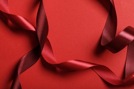 Close up di seta curva bordeaux e nastri rossi su sfondo rosso Archivio Fotografico