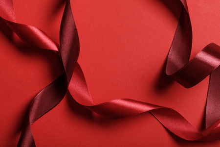 close up of curved silk burgundy and red ribbons on red background